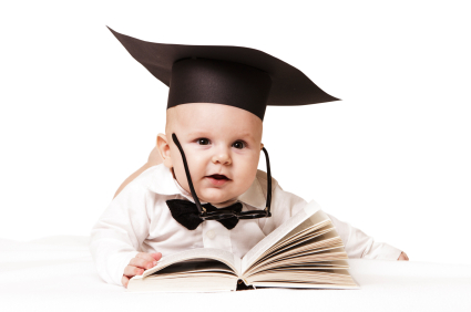 Infant reading book wearing graduation cap
