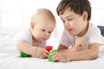 A baby and a young boy playing with toys