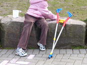 Child playing with chalk near crutches