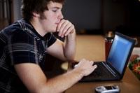 Teen boy using laptop computer