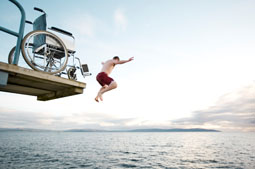 Boy jumping from wheelchair into lake