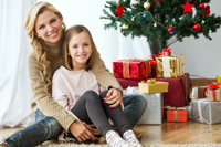Mother and daughter by Christmas tree