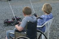 Two children playing with remote control cars, one is in a wheelchair, one is not