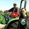 Girl standing next to man in tractor, video still shot